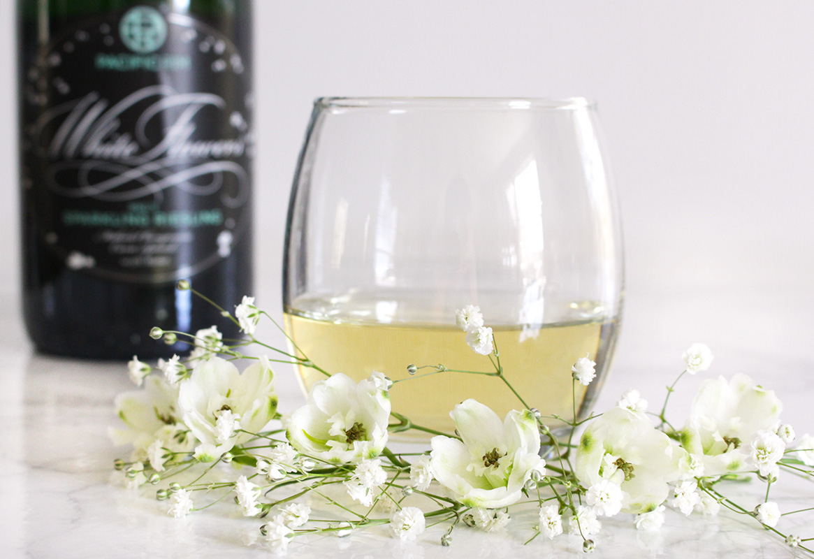 white wine glass with white flowers and Pacific Rim White Flowers bottle