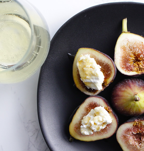 White wine glass with figs, cheese, and honey drizzle