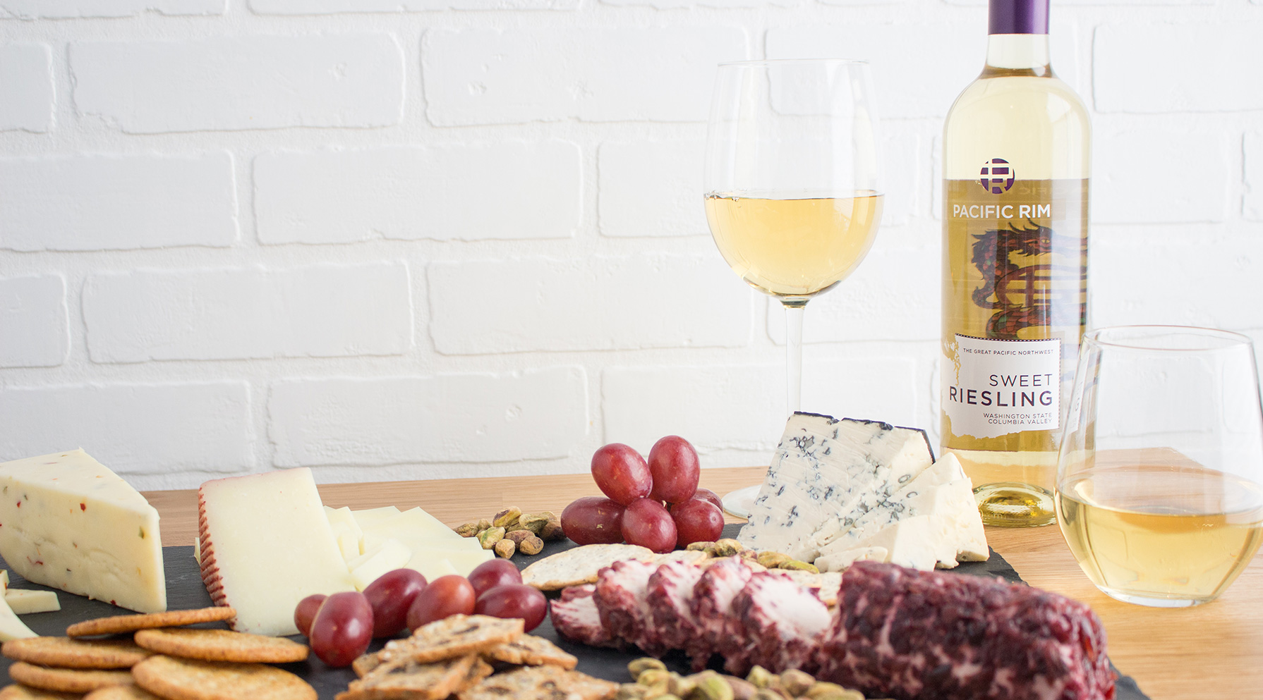 cheese platter, pacific rim wine bottle, and glass of wine