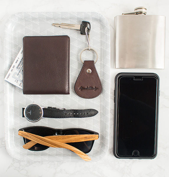 Overhead view of Osgoode Marley men's wallet on a tray with car keys, male watch, sunglasses, flask, and iPhone