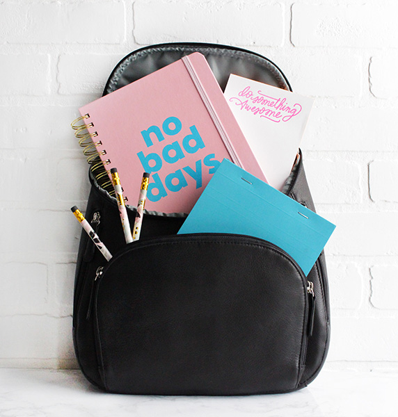 Black Osgoode Marlely backpack with pencils and colorful notebooks popping out