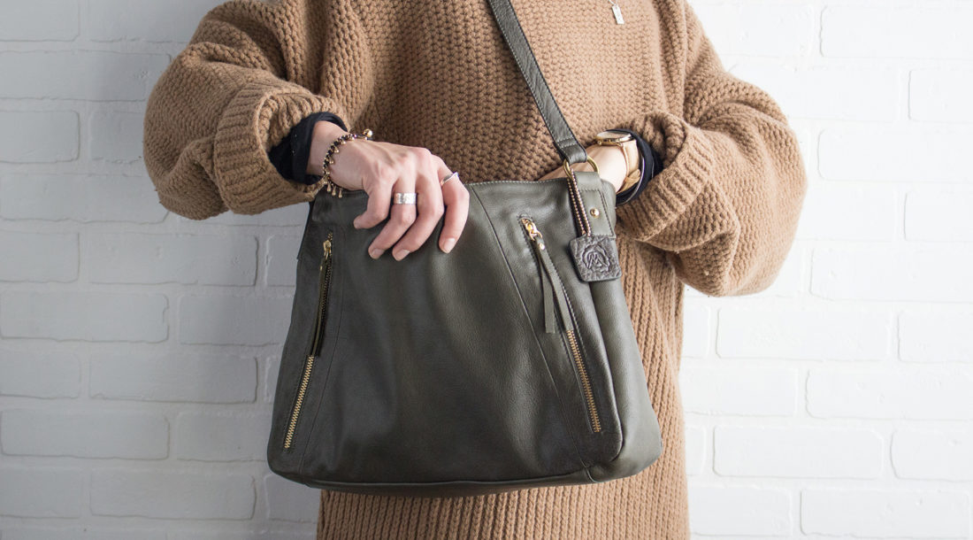 Girl opening Osgoode Marlely bag in front of brick wall