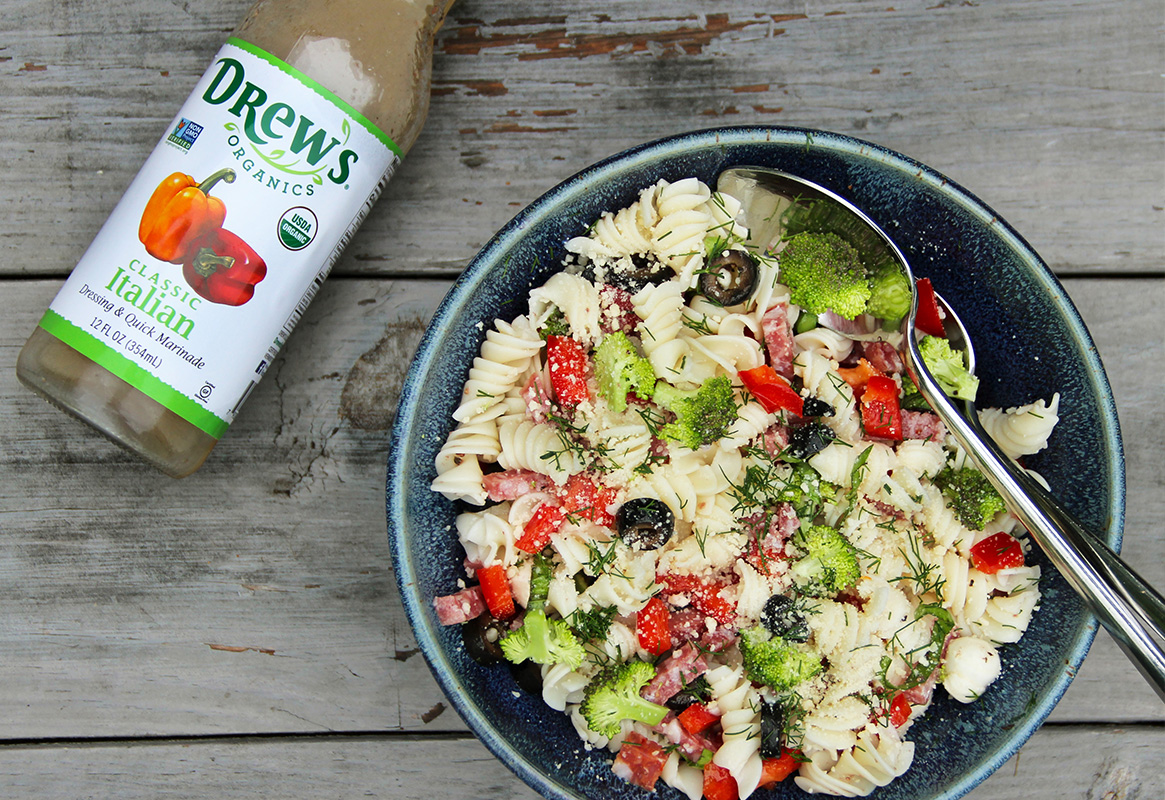 Overhead view of pasta salad in a blue bowl next to a bottle of Drew's Organics Classic Italian Dressing
