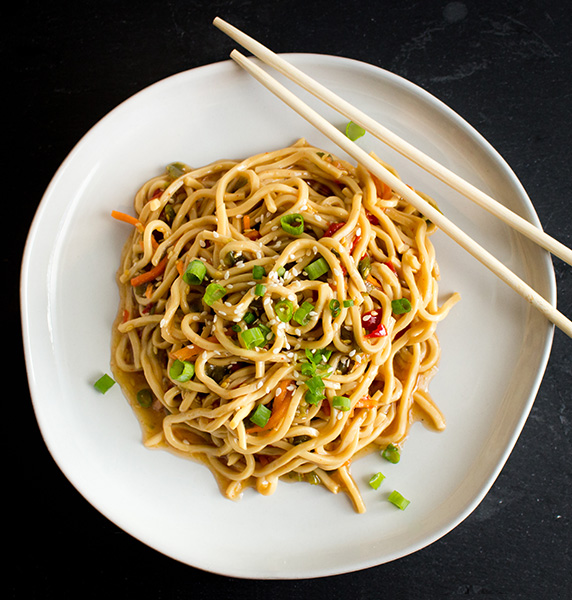 Overhead view of lo mein noodles on a white bowl with chop sticks