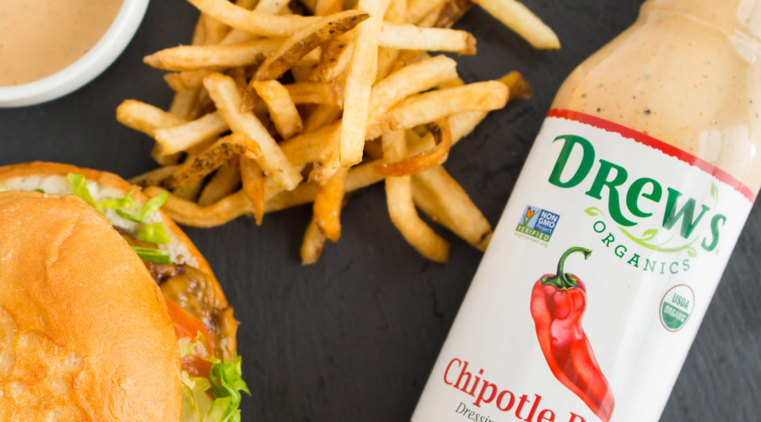 Overhead view of a cheeseburger and fries next to a bottle of Drew's Organics Chipotle Ranch Dressing
