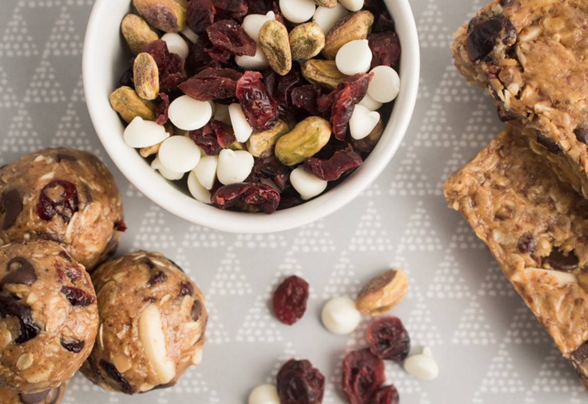 energy bites, granola bar, trail mix with cranberries, white chocolate chips, and pistachios on a platter
