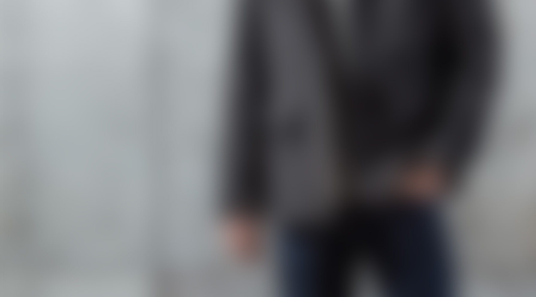 blurred image of a man's torso wearing a grey jacket and blue jeans